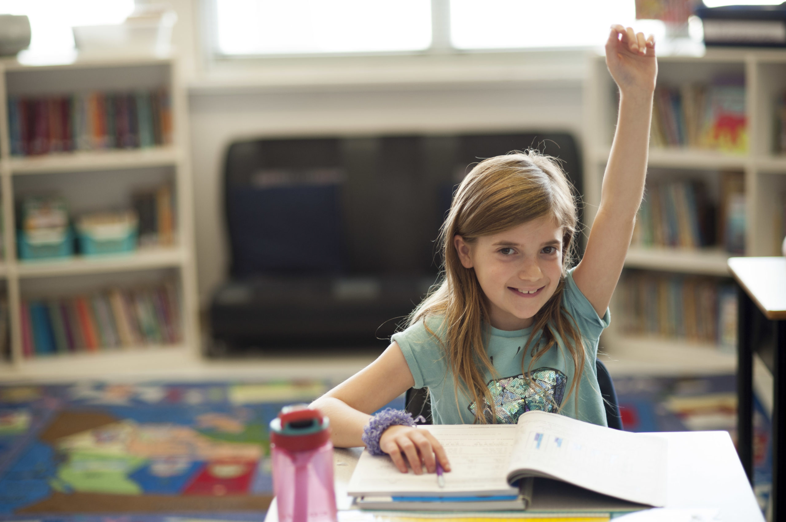 Smiling child in a classroom with hand raised